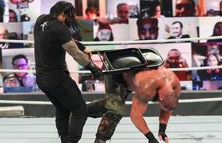 Reigns beat down Strowman with a chair