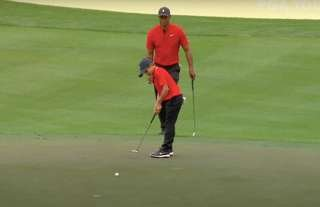 Tiger Woods watching his son Charlie putt