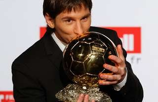 Barcelona's Messi kisses one of his first Ballon d'Or trophies.