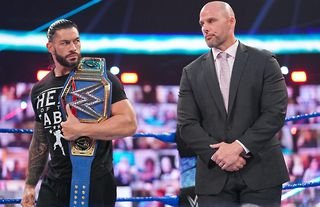 Roman Reigns and Adam Pearce