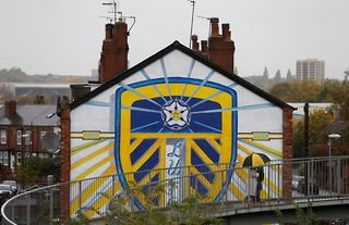 A mural of the Leeds United crest on the side of a house