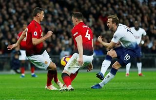 Manchester United players Phil Jones and Nemanja Matic attempt to tackle Tottenham's Harry Kane at Wembley in the Premier League