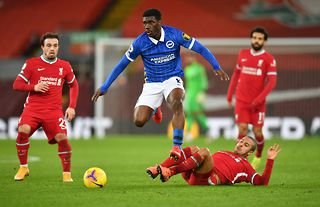 Brighton midfielder Yves Bissouma is tackled by Liverpool's Thiago in a Premier League game at Anfield