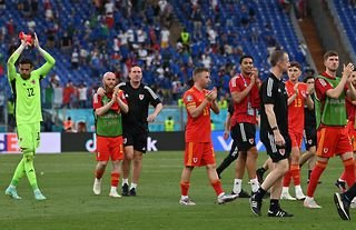 Wales' players clap their supporters