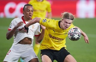 Erlng Haaland competes with Jules Kounde in the Champions League