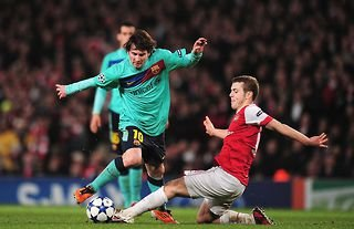 Jack Wilshere of Arsenal tackles Barcelona star Lionel Messi in the Champions League in 2011