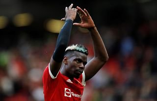 Man United midfielder Paul Pogba with his arms in the air